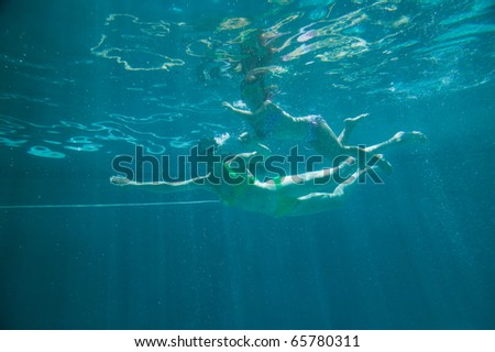 Mother and daughter in swimming pool under water