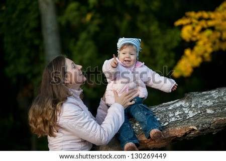 Mother and daughter in the autumn park - stock photo