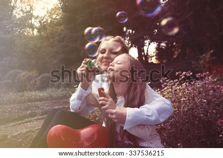mother and daughter in the autumn park blowing bubbles - stock photo
