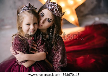 mother and daughter in the image of the queen and princess dresses in the colors of Marsala with a long train in the loft