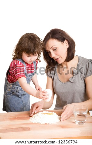 mother and daughter in the kitchen making a dough - stock photo