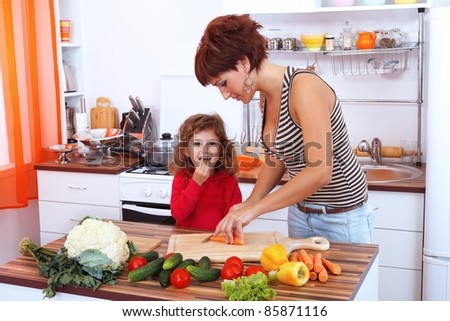 Mother and daughter in the kitchen preparing a salad