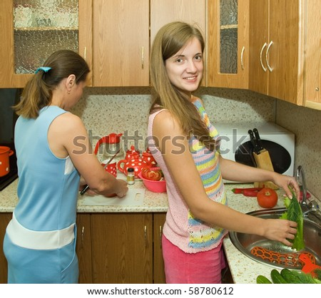 mother and daughter in the kitchen with some vegetables - stock photo