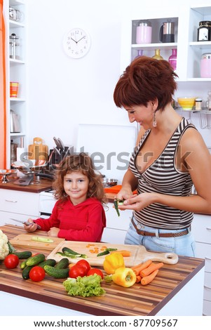 Mother and daughter in the kitchen with vegetables - stock photo