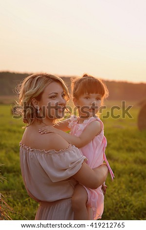 Mother and daughter in the same style  a field, sunset light. Tenderness