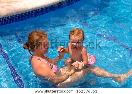 Mother and daughter in the swimming pool holding each other, having fun time
