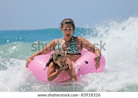mother and daughter in the waves - stock photo
