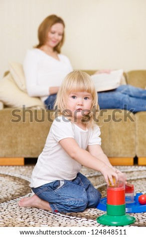 Mother and daughter indoors. girl looking at camera - stock photo