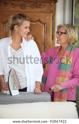 Mother and daughter ironing - stock photo