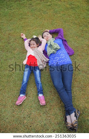Mother and daughter is happily smiling together laying on the grass yard. - stock photo