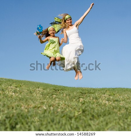 mother and daughter jumping - stock photo