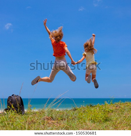mother and  daughter jumping at the beach in the day time - stock photo