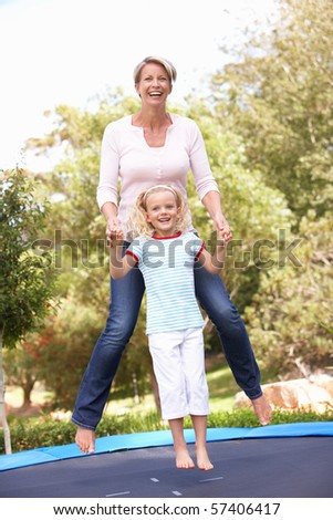 Mother And Daughter Jumping On Trampoline In Garden - stock photo