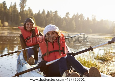 Mother and daughter kayaking on rural lake, close up - stock photo
