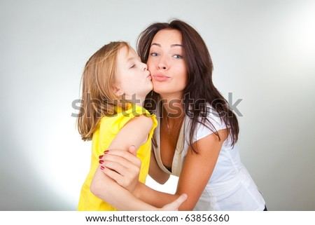 Mother and daughter kiss - stock photo