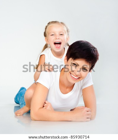 Mother and daughter laughing and looking at camera - stock photo