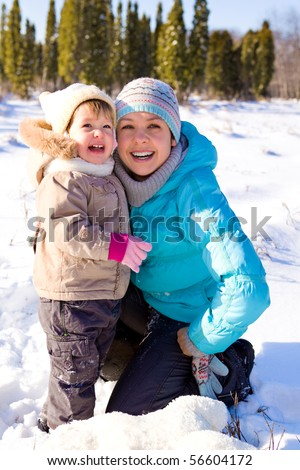 Mother and daughter laughing in a winter park - stock photo