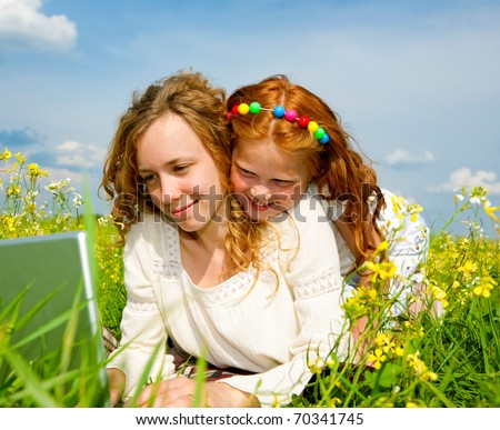 mother and daughter lay on grass with notebook - stock photo