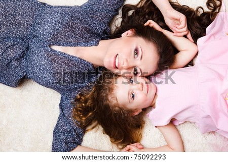 Mother and daughter laying close to each other - stock photo