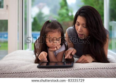 Mother and daughter laying on couch playing with a digital tablet - stock photo