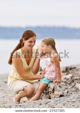 Mother and daughter listening to seashell at beach - stock photo