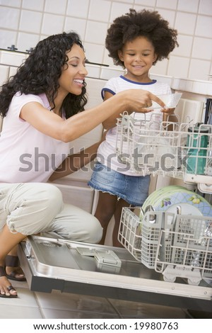 Mother And Daughter Loading Dishwasher - stock photo