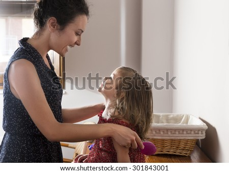 Mother and daughter look at each other smiling and happy. Woman combing the hair of little girl in the morning. Concept of family and happiness - stock photo