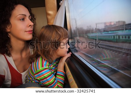 mother and daughter look in train`s window - stock photo