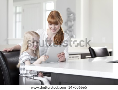 Mother and daughter looking at a digital tablet - stock photo