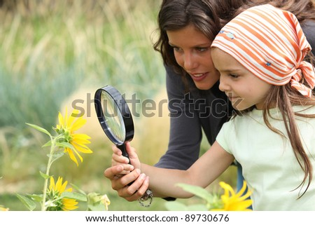Mother and daughter looking at a flower with a magnifying glass - stock photo