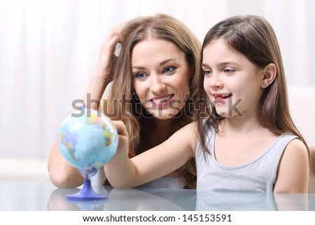 Mother and daughter looking at a globe  - stock photo