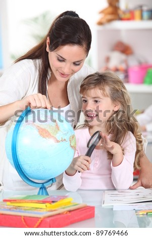 Mother and daughter looking at a globe with a magnifying glass - stock photo