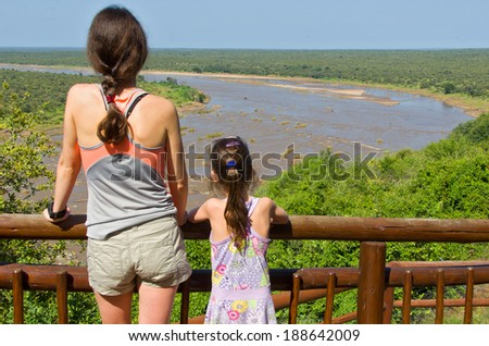 Mother and daughter looking at beautiful river view, tourists travel in South Africa, Kruger national park  - stock photo