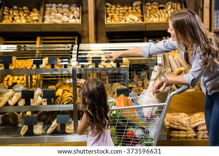 Mother and daughter looking at bread in grocery store - stock photo