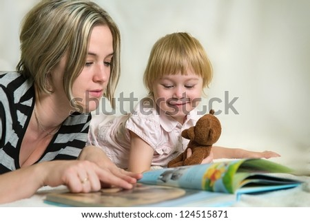 Mother and daughter looking at children's book - stock photo