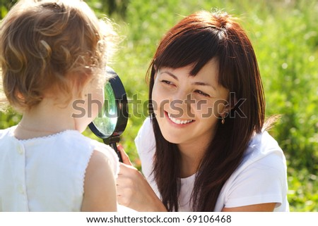 Mother and daughter looking at each other through a magnifying glass - stock photo