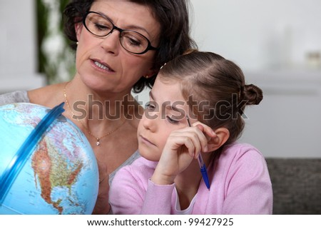 Mother and daughter looking at globe - stock photo