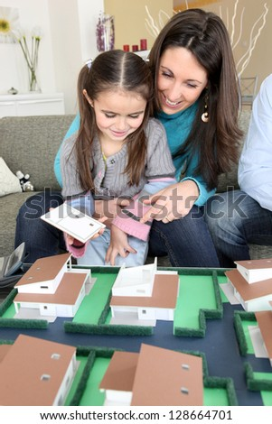 Mother and daughter looking at housing - stock photo
