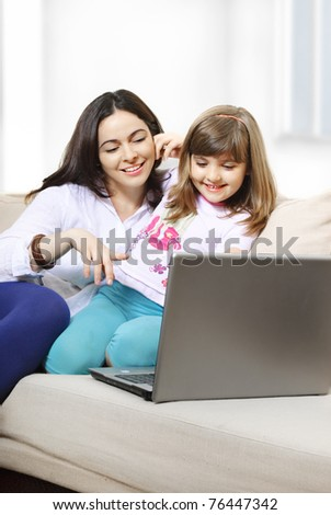 Mother and daughter looking at laptop and smiling - stock photo