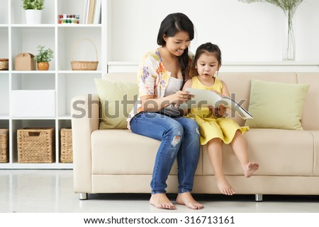 Mother and daughter looking at pictures in the magazine - stock photo