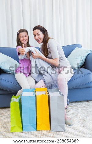 Mother and daughter looking at shopping bags at home in the living room - stock photo