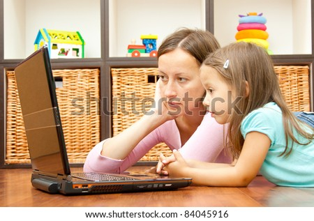 mother and daughter looking the laptop - stock photo