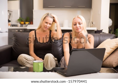 Mother and Daughter looking things up on a laptop computer. - stock photo