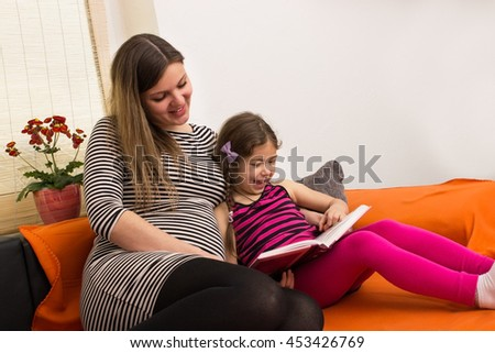 Mother and daughter looking together in a book - stock photo