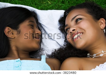 Mother and daughter lying in the grass having fun - stock photo