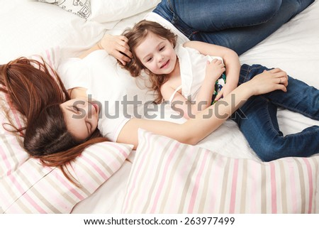 mother and daughter lying on the bed and smiling - stock photo