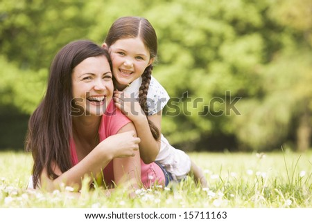 Mother and daughter lying outdoors smiling