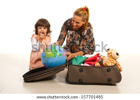 Mother and daughter make their luggage for travel - stock photo