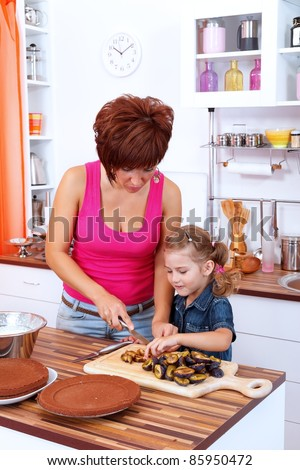 Mother and daughter making a cake with damson plums - stock photo
