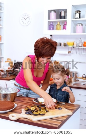 Mother and daughter making a cake with damson plums in the kitchen - stock photo